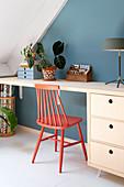 Korallrot bemalter Sprossenstuhl am Schreibtisch vor blauer Wand