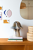 Mushroom-shaped, marbled table lamp on stacked books