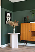 Two-tone dark green wall in room decorated in mid-century modern style