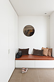 Brown scatter cushions on upholstered bench in hallway with fitted cupboards