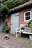 Boy sitting on garden bench next to wooden crates outside brick house