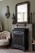 An antique mirror on the mantelpiece above a cast iron stove