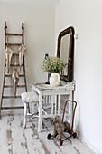 Weißer Tisch mit Hocker in Shabby-Style, Wandspiegel und Leiter mit alten Regenschirmen
