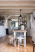 Holztisch mit verschiedenen Sitzmöbeln und alter Apothekerschrank in offenem Wohnraum