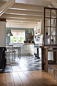 A view into a kitchen with a chequerboard floor and a wooden ceiling
