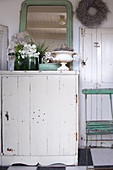 Blumen und Spiegel auf altem, weißem Schrank