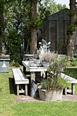A wooden table with benches and planters in a garden