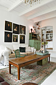 An old wooden table, a light covered sofa and a portrait painting in a living room