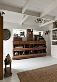 An antique wooden cabinet with drawers and shelves in a room with white floorboards