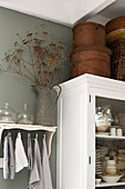 Storage boxes on a white cupboard next to a zinc jug of a dried flowers on a shelf