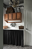 Suitcases and zinc jugs on a wooden wall cupboard with storage space behind a curtain