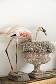 A stuffed flamingo and an antique urn