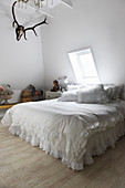 A double bed with white ruffles in a bedroom with deer antlers on the wall