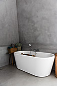 A freestanding bathtub in front of a grey wall