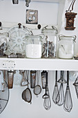Storage jars and vintage kitchen utensils on a white shelf