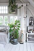 Mariastatue und Topfpflanze vor Schrank mit Lamellentür in weißem Wohnzimmer in Shabby-Style