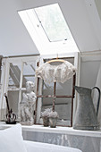 Old window frames and shabby-chic style decorative objects below a skylight