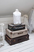A stack of vintage suitcases and a dressmaker's dummy in an attic