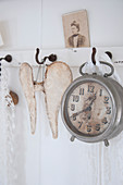 A vintage alarm clock and a pair of wings on hooks