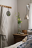 A bedside table next to a bed and a row of hooks in a rural bedroom