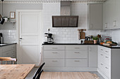 A fitted kitchen with light grey cabinet fronts and subway tiles on the wall