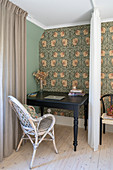 A black desk with a wicker chair behind a curtain in guest room with wallpaper