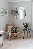 Rattansessel, Beistelltisch, Stehlampe und runder Spiegel an der Wand mit gemusterter Tapete