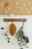 Leaves hanging from wooden rack on wall