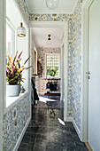 A narrow hallway with a window and floral wallpaper