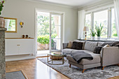 A grey upholstered sofa on a matching carpet in an open-plan living room