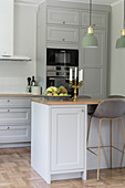 A kitchen with grey cupboard fronts and a breakfast bar with a bar stool