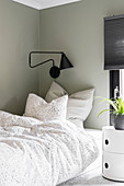 A single bed, a reading lamp and a classic bedside table in a boy's room