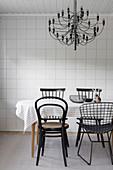 Essbereich mit verschiedenen Stühlen und Kronleuchter vor gefliester Wand