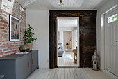 A grey painted sideboard against a brick wall in an entrance area with a white painted wooden floor