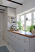 A white Scandinavian-style kitchen with a wooden worktop