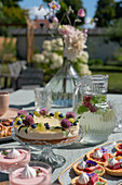 Cakes, tarts and dessert glasses on a table laid on a terrace