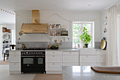 A white kitchen work surface with a gas hob and a brass extractor hood
