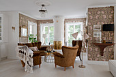 Antique upholstered furniture and a Swedish tiled stove in a living room with floral wallpaper