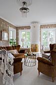 Antike Polstergarnitur und schwedischer Kachelofen im Wohnzimmer mit Blumentapete