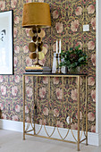 A lamp on a filigree console table against a wall with floral wallpaper