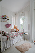 A bed with a floral cover in a white painted bedroom for a girl