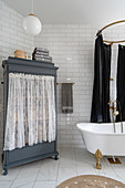 A cupboard with a curtain and a freestanding bathtub in a bathroom with white subway tiles
