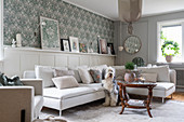 A light upholstered corner sofa in a living room with wood panelling and wallpaper