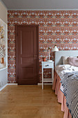 A door next to a double bed in a wallpapered bedroom