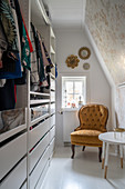 An antique upholstered chair in a walk-in closet