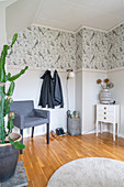 An armchair, a coat rack and a bedside table in a room with bird wallpaper on the wall