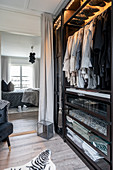 A walk-in wardrobe with access to a bedroom