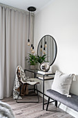 A dressing table, a round wall mirror, a pendant lamp and an upholstered bench in a bedroom