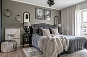 A double bed in a bedroom with a taupe wall