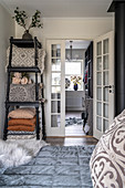 A view from a bed of pillows on a shelf and a walk-in closet